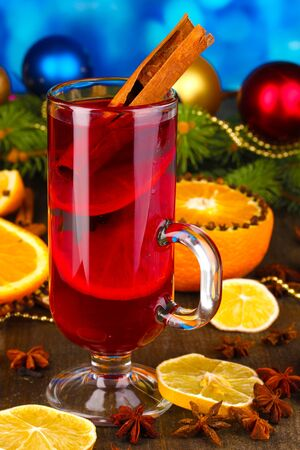 Fragrant mulled wine in glass with spices and oranges around on wooden table on blue background photo