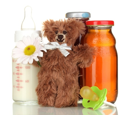 Baby food, bottle of milk and juice with teddy bear isolated on white photo