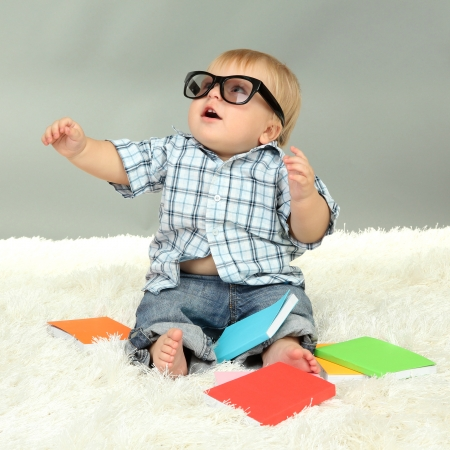 Little boy with multicolor books, on white carpet photo