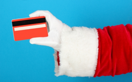 Santa Claus hand holding red credit card on blue background Stock Photo - 17403775