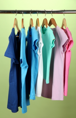 Variety of casual shirts on wooden hangers,on blue background photo