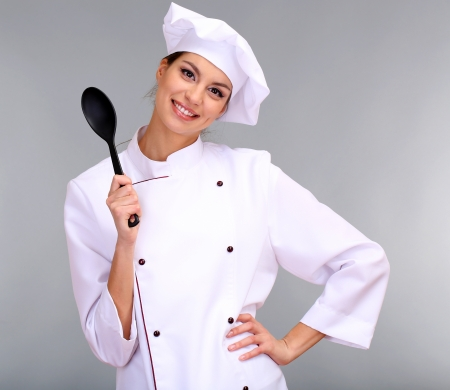 culinary skills: Portrait of young woman chef on grey background Stock Photo