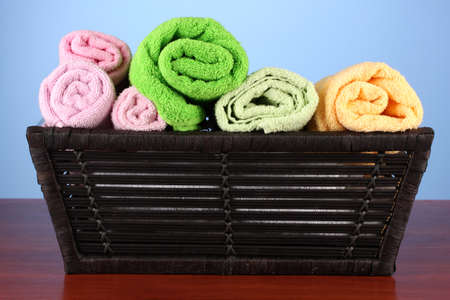 Colorful towels in basket on color background photo