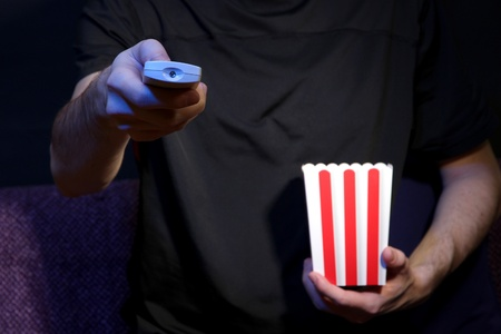 Man hand holding a TV remote control and popcorn, on dark background photo