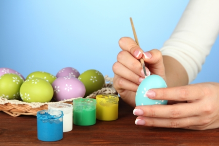 Young woman painting Easter eggs, on color background Stock Photo - 17403796