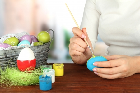 Young woman painting Easter eggs, on bright background Stock Photo - 17403862
