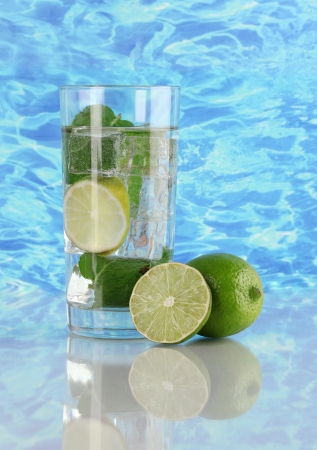 Glass of water with ice, mint and lime on sea background Stock Photo - 17403805