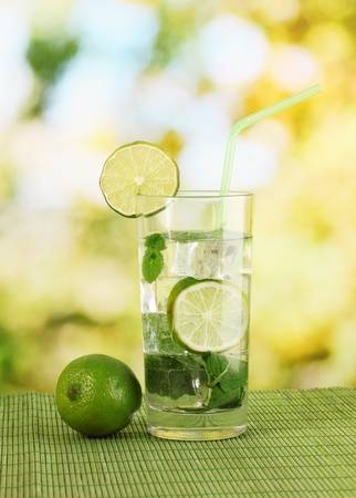 Glass of water with ice, mint and lime on table on bright background Stock Photo - 17403855