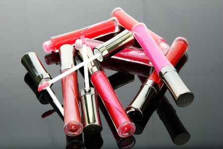 applicator: beautiful lip glosses with rose petals, on grey background