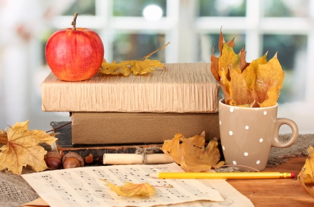 Autumnal composition with gift, books and leaves on bright background photo