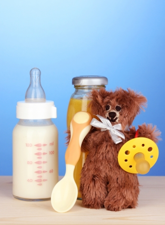 Baby bottle of milk, juice and teddy bear on blue background Stock Photo - 17403808