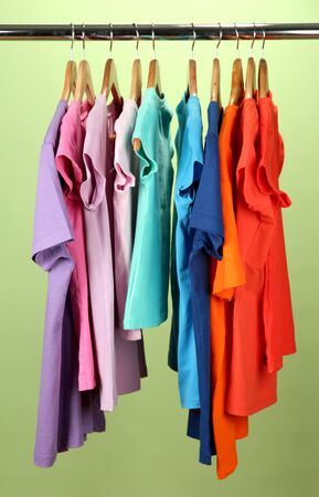 clothing rack: Variety of casual shirts on wooden hangers,on green background