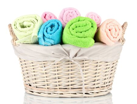 Colorful towels in basket isolated on white photo