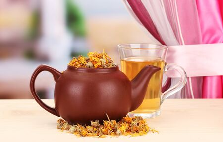 Dried herbs in teapot on wooden table, on bright background. Conceptual photo of herbal tea. photo