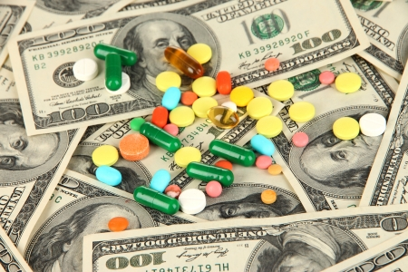 health care funding: Pills and money close-up background Stock Photo