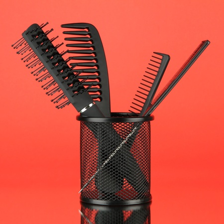 Iron basket with combs and hair brush, on color background photo