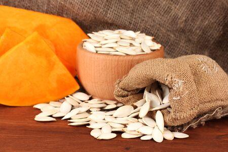 Pumpkin seeds in sack, on wooden background photo