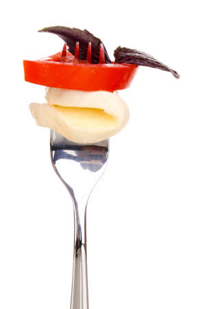 tasty mozzarella with tomatoes on fork isolated on white photo