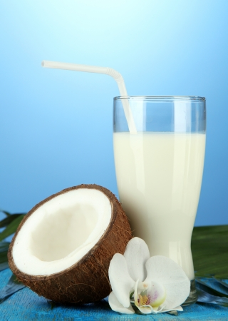 Coconut with glass of milk,  on blue background photo