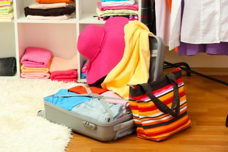 Open silver suitcase with clothing in room Stock Photo - 17459572