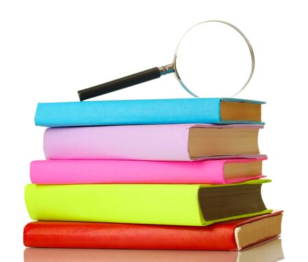Magnifying glass and books isolated on white photo