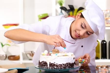 若い女性シェフの台所でケーキ