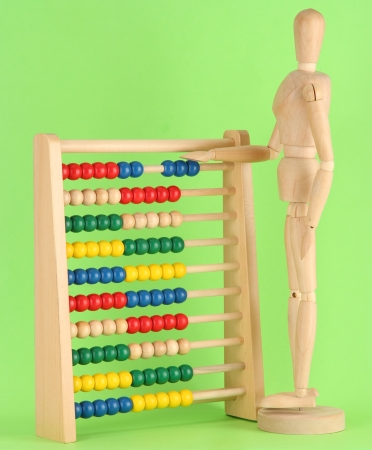 Bright toy abacus and wooden dummy, on green background Stock Photo - 17463352