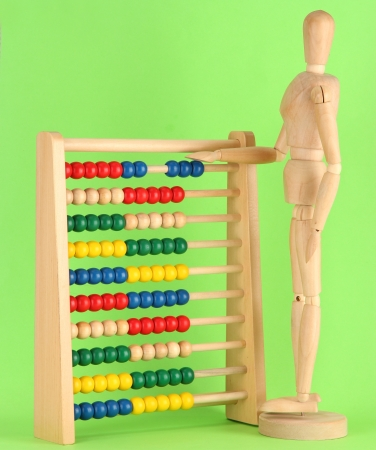 Bright toy abacus and wooden dummy, on green background Stock Photo - 17463348