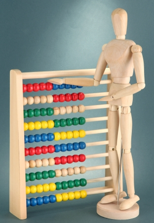 Bright toy abacus and wooden dummy, on grey background Stock Photo - 17463356