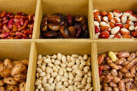 Diverse beans in wooden box sections close-up photo