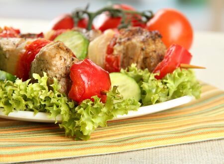tasty grilled meat and vegetables on skewer on plate, on table photo