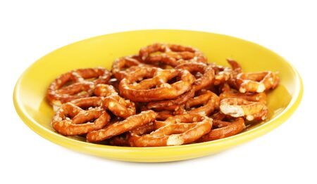 Tasty pretzels in yellow plate isolated on white Stock Photo - 17485556