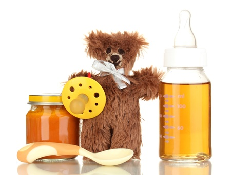 Baby bottle with fresh juice, puree and teddy bear isolated on white photo