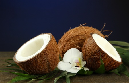 Coconuts with leaves and flower, on wooden table on blue background Stock Photo - 17485904