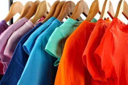 tienda de ropa: La elección de ropa de diferentes colores en perchas de madera, aislado en blanco Foto de archivo
