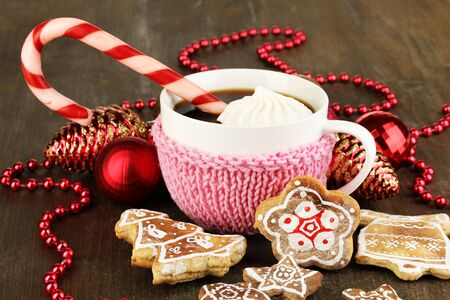 Cup of coffee with Christmas sweetness on wooden table close-up photo