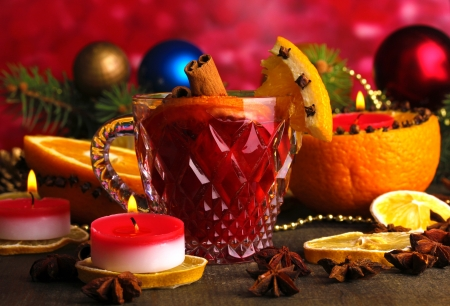 Fragrant mulled wine in glass with spices and oranges around on wooden table on red background photo