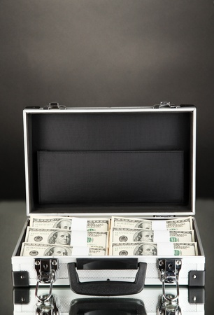 Suitcase with 100 dollar bills on black background photo