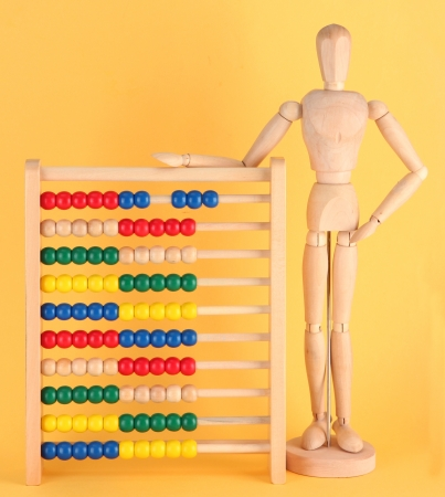 Bright toy abacus and wooden dummy, on yellow background Stock Photo - 17485613