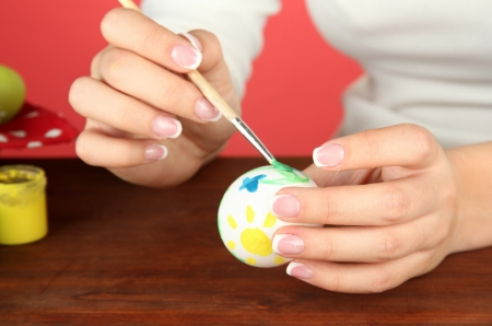 Young woman painting Easter eggs, on color background Stock Photo - 17485756