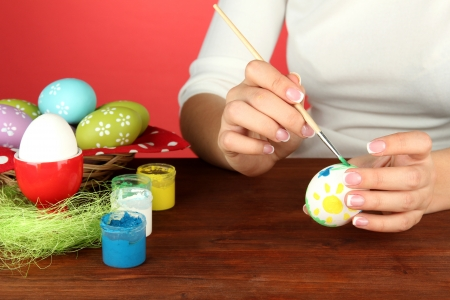 Young woman painting Easter eggs, on color background Stock Photo - 17486030