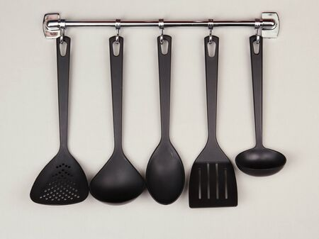 Black kitchen utensils on silver hooks, on grey background photo