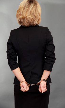 Young beautiful business woman in handcuffs on grey background photo