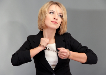handcuffs woman: Young beautiful business woman in handcuffs on grey background Stock Photo