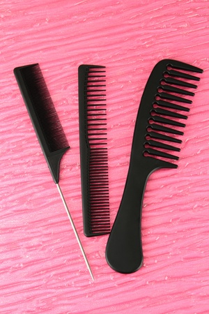 Black combs on color background photo
