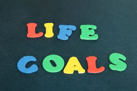 Phrase LIFE GOALS in colorful letters on school board close-up photo