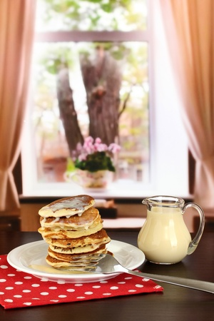 rubicund: Sweet pancakes on plate with condensed milk on table in room Stock Photo