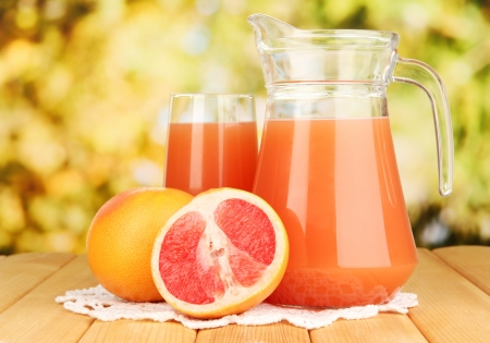 Full glass and jug of grapefruit juice and grapefruits on wooden table outdoor photo