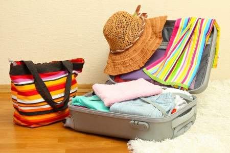 belongings: Open silver suitcase with clothing in room