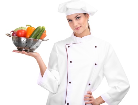 culinary skills: Portrait of young woman chef with vegetables isolated on white